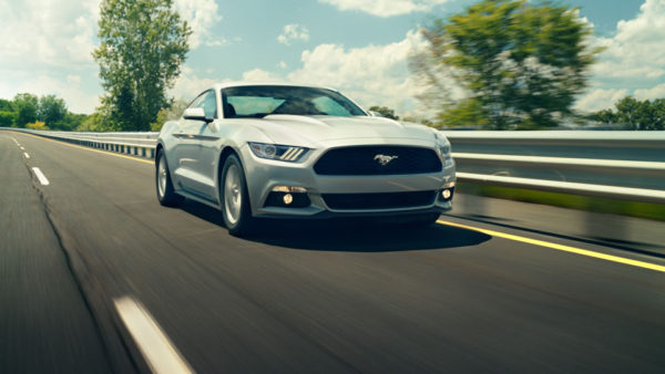 White Ford Mustang speeding down a highway