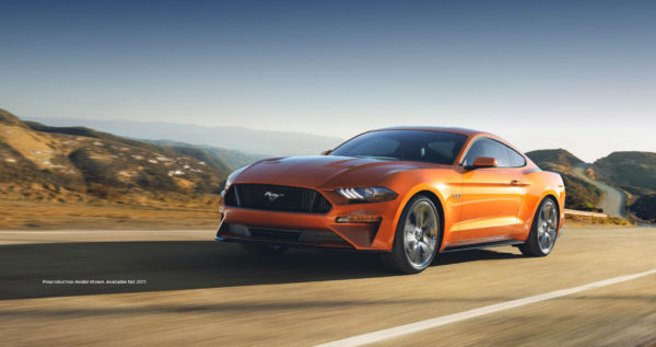 An orange 2018 Ford Mustang driving down a road surrounded by mountains