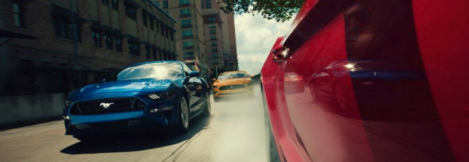 Three 2018 Ford Mustang cars driving down the road together