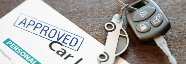 A set of keys on top of an approved car loan featured in a blog post about bad credit car loans